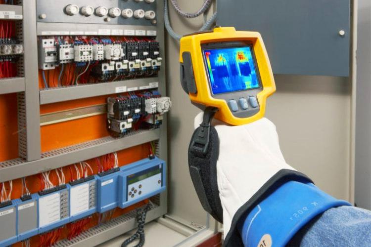 illustration montrant un professionnel qui utilise une caméra thermique pour vérifier un compteur electrique